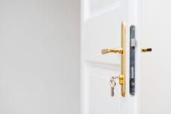 在匙孔的钥匙与美丽的金黄门把 免版税库存照片