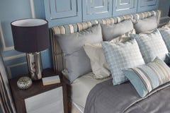 在区别样式的浅兰的枕头与经典样式卧室 库存照片
