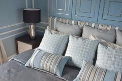 在区别样式的浅兰的枕头与经典样式卧具 免版税图库摄影
