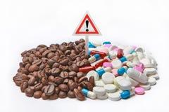 在医学和警告惊叹号旁边的咖啡豆 图库摄影