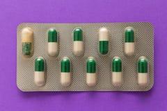 在医学箱子的过期的白色和绿色胶囊 在lav的药片 库存图片