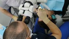 在医生的顶视图使用显微镜 治疗现代牙齿诊所的牙医患者 正牙医生与一起使用 股票录像