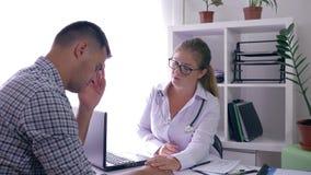 在医疗办公室供以人员健康,女性医生支持不快乐的男性患者 影视素材