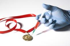 在医疗手套的一只手刺中与普遍的红色类固醇的一枚金牌在白色背景的注射器 免版税库存照片