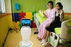 在医疗谈话的机器人服务与耐心室的患者我 免版税库存图片