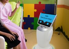 在医疗谈话的机器人服务与耐心室的患者我 免版税库存照片