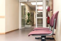 在医院地板的空的椅子 图库摄影