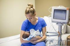 在医院照顾抱着她新出生的早产儿 免版税库存照片