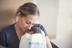 在医院照顾抱着她新出生的早产儿 免版税库存图片