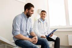 在医院的微笑的医生和年轻人会议 库存照片