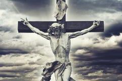 在十字架上钉死。与耶稣基督雕象的基督徒十字架在风暴 免版税库存照片