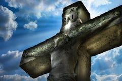 在十字架上钉死在天空背景的耶稣基督雕象 免版税图库摄影