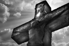 在十字架上钉死在天空背景的耶稣基督雕象 免版税库存图片