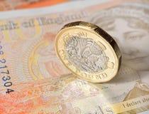 在十磅笔记的新的1英镑硬币 免版税库存图片