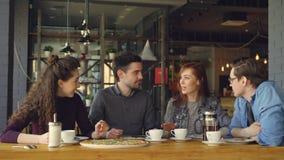 在午休期间,友好的同事谈话在桌上在薄饼房子里 茶壶和杯子,大可口薄饼和 股票录像