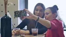 在午餐期间,两美丽的年轻女人放松,坐在咖啡馆 做selfies在您的智能手机 企业咖啡杯方便问题午餐开张了 影视素材