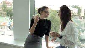 在午餐期间,工作在银行中的两个企业女孩由窗口喝咖啡并且沟通 工作,咖啡,通信 影视素材