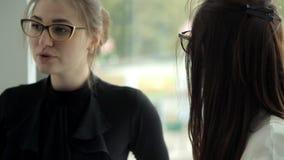 在午餐期间,工作在银行中的两个企业女孩由窗口喝咖啡并且沟通 工作,咖啡,通信 股票视频