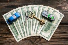 在半圆布局的几100美元钞票与一个回归键和年迈的概略的木表面上的玩具汽车 免版税库存图片