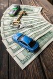 在半圆布局的几100美元钞票与一个回归键和年迈的概略的木表面上的玩具汽车 免版税图库摄影