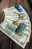 在半圆布局的几100美元钞票与一个回归键和年迈的概略的木表面上的玩具汽车 免版税库存照片
