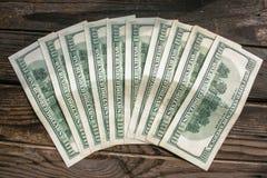 在半圆布局的几100美元钞票在年迈的粗砺的木窗台 库存照片