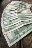 在半圆布局的几100美元钞票在年迈的粗砺的木窗台 免版税库存照片