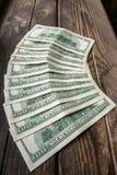 在半圆布局的几100美元钞票在年迈的粗砺的木窗台 免版税库存图片