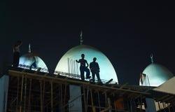 在半夜工作在deira,迪拜,阿拉伯联合酋长国的建筑工人 库存照片