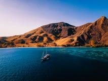 在半被烧的海岛前面的Diveboat在印度尼西亚,科莫多国家公园 寄生虫射击 免版税库存照片