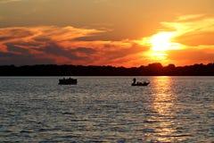 在华盛顿湖的日落有浮船和渔船的 库存图片
