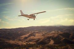 在华美的日落天空的小单引擎飞机飞行在壮观的山上 库存照片