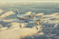 在华美的日落天空的小单引擎飞机飞行通过云彩海在壮观的山上的 库存图片
