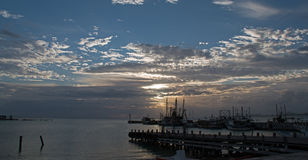 在华雷斯港坎昆墨西哥渔船/拖网渔船和船坞和码头和跳船和防波堤的日出 库存照片