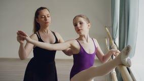 在单独教训期间,芭蕾老师专业芭蕾舞女演员教女孩胳膊运动并且弯曲在芭蕾纬向条花 股票视频