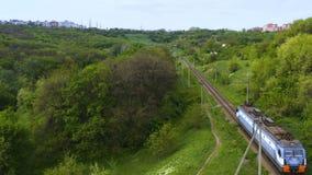 在单独继续前进铁路的电车机车的鸟瞰图通过foresty小山 影视素材