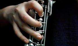 在单簧管的妇女手 免版税库存图片
