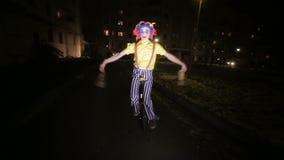 在单轮脚踏车的哀伤的可怕小丑骑马在一条黑暗的街道 股票录像
