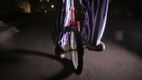 在单轮脚踏车的哀伤的可怕小丑骑马在一条黑暗的街道 影视素材