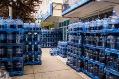 在卖主前面的被装瓶的饮用水 免版税库存照片