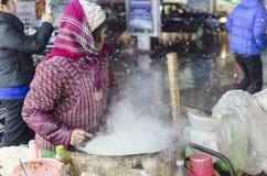 在卖妇女的街道的斯诺伊夜做薄煎饼 免版税库存图片