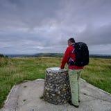 在南下来方式小径的多云阴暗夏天日出从有背包的中部年迈的男性步行者敬佩看法的 免版税库存图片