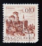 在南斯拉夫打印的邮票在Gradacac显示修道院和一个回教清真寺有尖塔的,波斯尼亚镇  库存图片