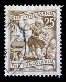 在南斯拉夫打印的邮票显示妇女对收获向日葵 免版税库存图片