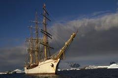在南极州的山的背景的帆船 免版税库存照片