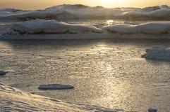 在南极洲的冰盖的海岛之间的海峡在sunse 免版税库存照片