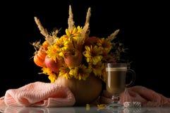 在南瓜、附近的杯热奶咖啡和在黑色隔绝的温暖的围巾的原始的秋天构成 免版税库存照片