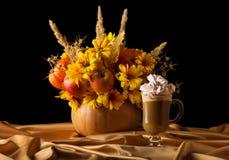 在南瓜和杯的原始的构成热奶咖啡用在丝织物的蛋白软糖,隔绝在黑色 图库摄影