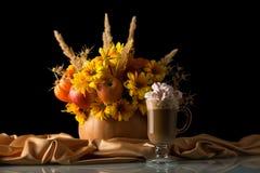 在南瓜的原始的花束在丝绸布料,杯子热奶咖啡用在黑色隔绝的蛋白软糖 免版税库存图片