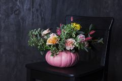 在南瓜花瓶的秋天百花香在黑椅子 免版税图库摄影